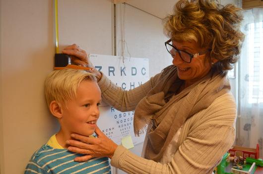 Helsesøster måler høyden på en gutt