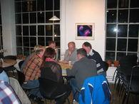 Sju personer sitter og diskuterer rundt et bord