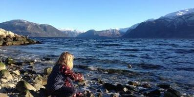 Barn som kastar stein i fjorden