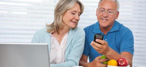 Eldre par ved PC og smarttelefon