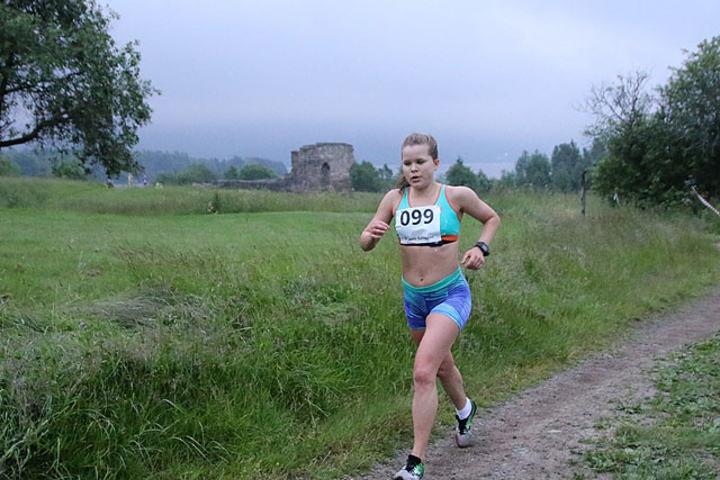 Tonje Gresslien med 1 km igjen å løpe. Bak henne ser vi Kirkeruinene og vi skimter såvidt Maridalsvannet som nesten går i ett med tåka som kom sigende. Foto: Heming Leira