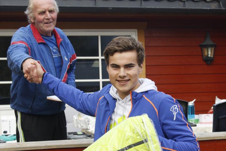 Vegard Øvrevik  blir gratulert med seieren av Arne Moren i Strandvoldbruas venner som nå har fått inn godt over en million kroner til bruprosjektet i nabolaget.