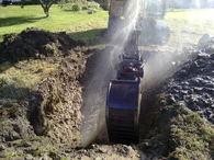 Gravemaskin og en lekk vannledning