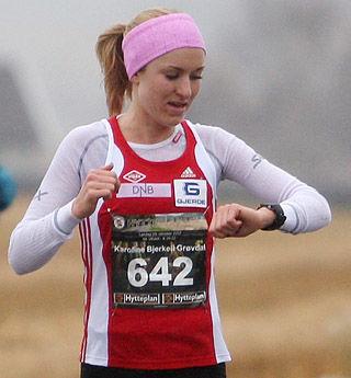 Mot rekord: Karoline Bjerkeli Grøvdal passerer 8 km-skiltet og sjekker passeringstida. Hun kan konstatere at hun ligger meget godt an. Kirsten Marathon Melkevik hadde den gamle løyperekorden på gode 33.20. Nå ble det en forbedring av rekorden med over ett og et halvt minutt.