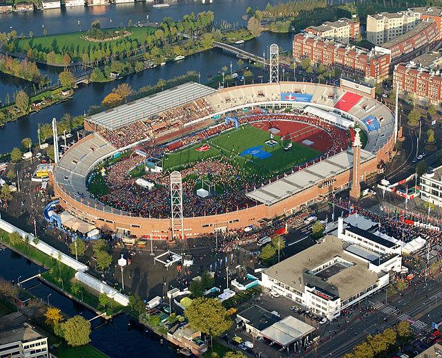 Olympisk stadion: Start og mål for Amsterdam Marathon er inne på stadion fra OL i 1928, som nå er ombygd og skal være arena for neste års EM i friidrett. Det er starten for maraton som er i gang på bildet og vi ser løpere på vei ut maratonporten ved stadiontårnet.