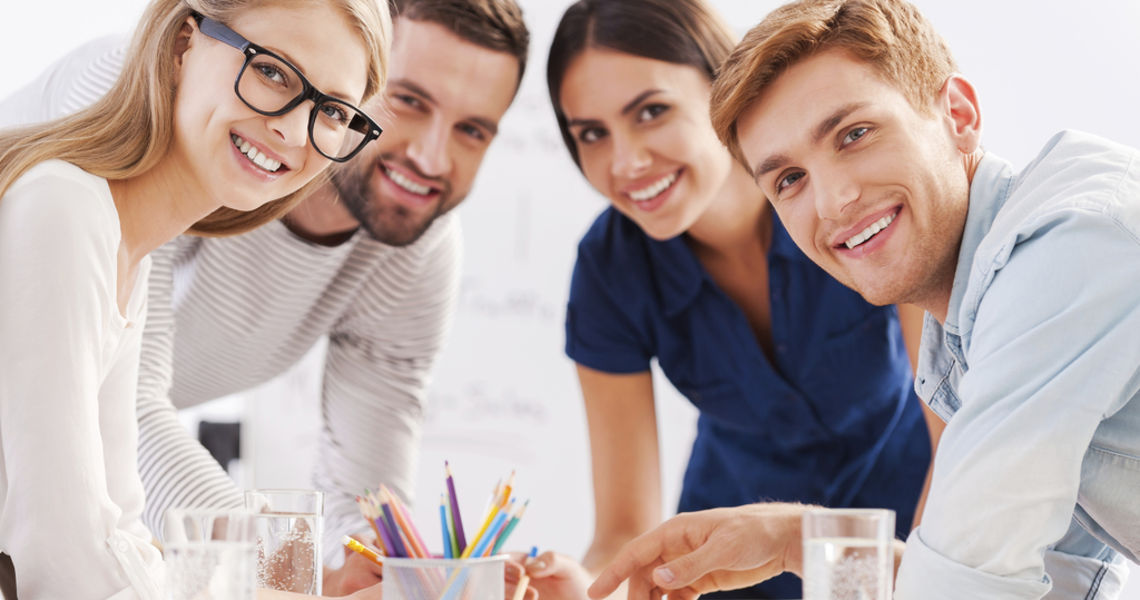 Young and creative team. Four cheerful business people in smart casual wear discussing something and smiling while leaning at the table