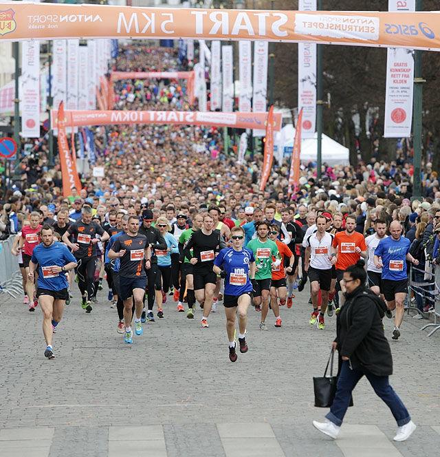 Starten på Sentrumsløpet ...og en fotgjenger. Puljen bak eliten er i gang. PS: Dama ble ikke løpt ned. Foto: Kjell Vigestad