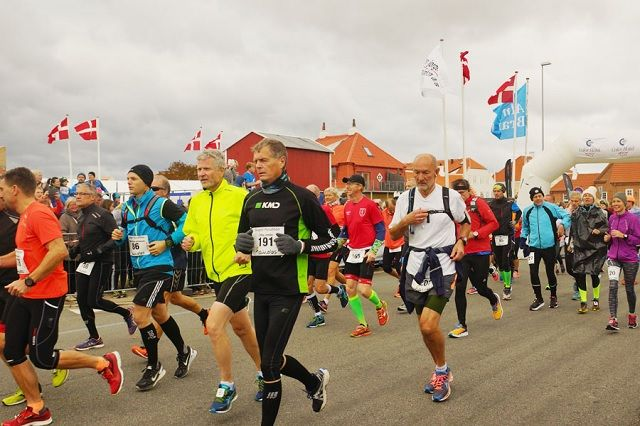 Flaggene vaier friskt i vinden når maratonløpere legger i vei i Skagen (Foto: Carsten Vestergaard).