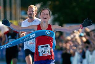 Hilde Aders jubler idet hun krysser mållinja som vinner av Oslo Maraton 2015. (Foto: Stian Schløsser Møller)