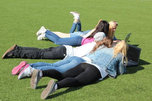 Ungdom ligger på gresset