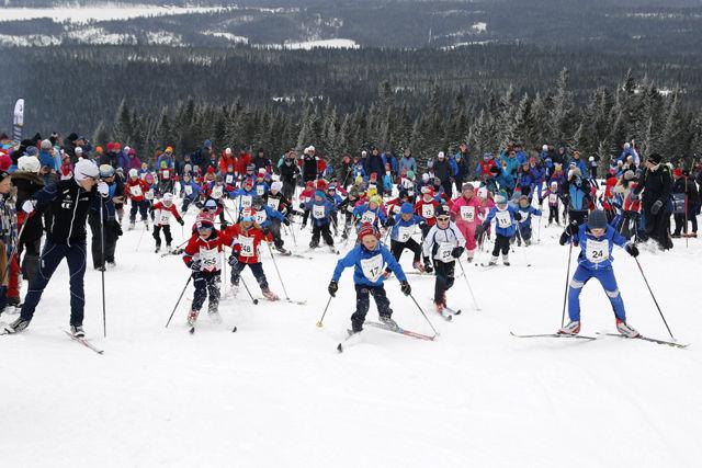 Simen Andreas Sveen heiet i gang 5-7-åringene opp Monsterbakken med Martin Johnsrud Sundby i bakgrunnen.