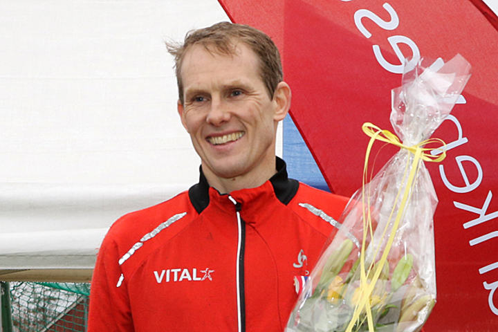 Svein Glomnes mottar premie og blomster etter å ha løpt inn til seier i NM terrengløp for veteraner.