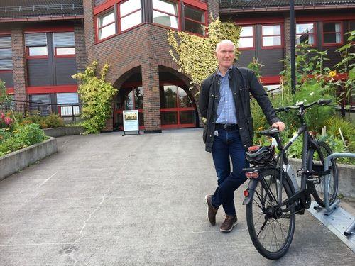 Rådmann Glemmestad med sykkel foran rådhuset