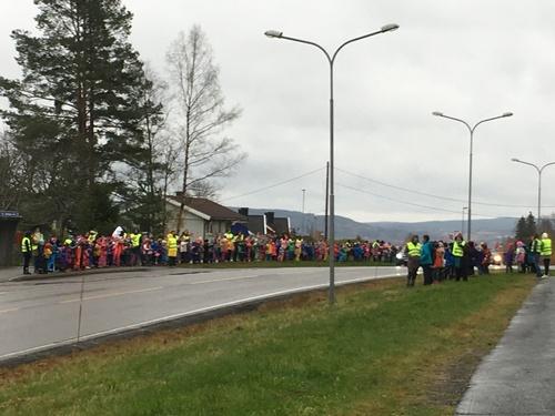 Barn og voksne langs veien ønsker Kongen velkommen