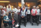 Eldre mennesker med startnummer og rullatorer, klar til å gå om kapp