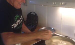 Mann som rører i grøt som står til koking