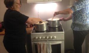 To damer rører i grøt som koker