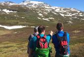 Tre menn som går tur i naturen og peker framover til målet