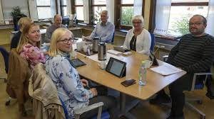 Mennesker rundt ett bord med møtepapirer