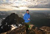 Mann på toppen av ett fjell med utsikt over fjorden