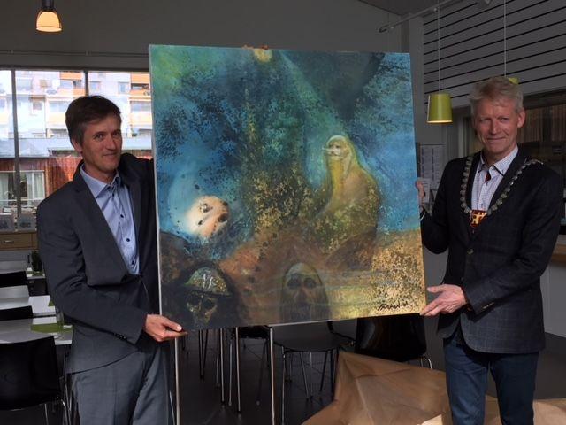 Anders Flaarønning holder maleriet bedriften har fått i gave sammen med ordfører Gunnar Krogstad.