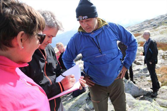 Øyvind Oddekalv signerer, medan Astrid Aarhus Byrknes og Per Ole Ekker følgjer nøye med.