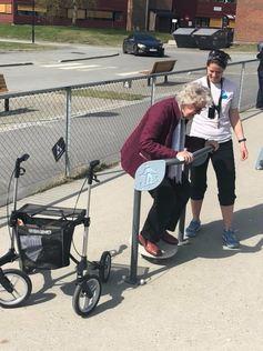 En eldre dame trener balanse på et treningsapparat. Hun får veiledning av helsepersonell.