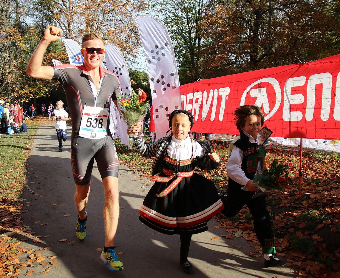 Joar Thele løper i mål som vinner i fjor, med bunadskledd blomsterpike ved siden av. Bygdøymilas svar på Vasaloppets kranskulla. (Foto: Heming Leira)