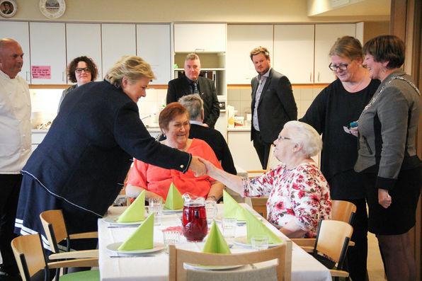 Statsminister Erna Solberg helsar på bebuarar ved Knarvik sjukeheim før middagen.