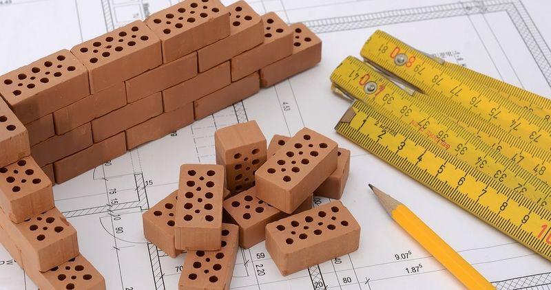 Bildet er et nærbilde av deler av en byggetegning, en tommestokk, blyant og små mursteiner.