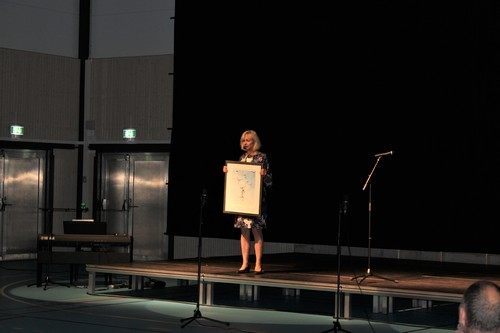 Rektor Elisabeth Aandalen viser frem bildegave Smestad skole
