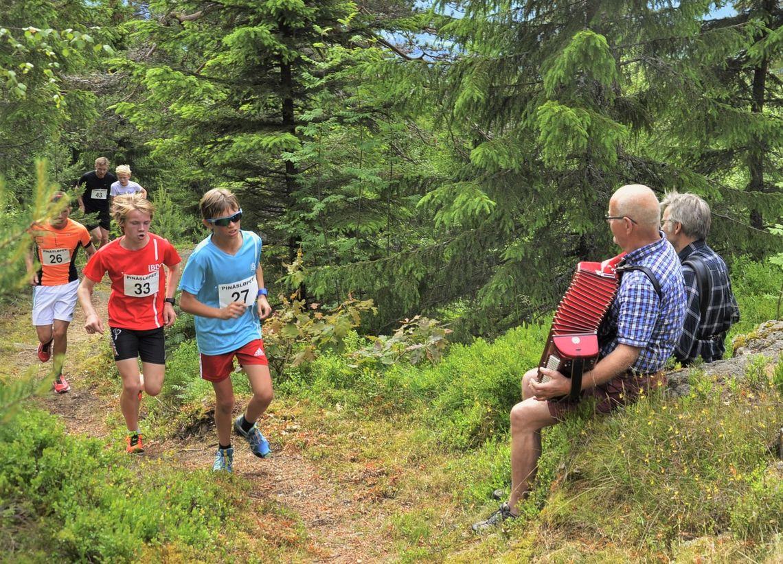 Rett før passering av Pinåstoppen i 2016 ble løperne møtt med trekkspilltoner fra Håvald Hustuft og Per Ståle Tjentland. (Foto: Langsveien.no)