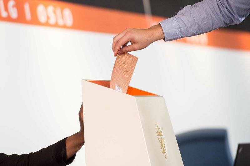 Illustrasjonsbilde av at en stemmeseddel blir lagt i urne under valg.