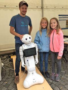 Bilde fra utstilling av en robot med to elever fra Brekkåsen skole