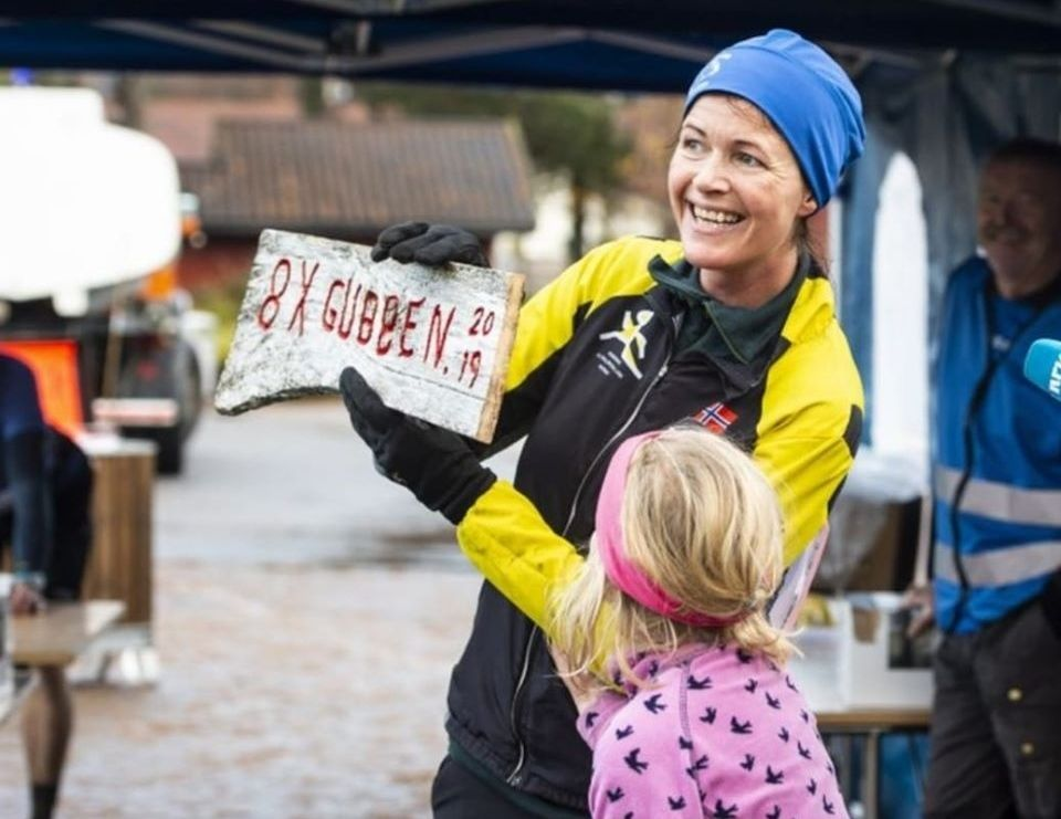 Øyunn Bygstad har fullført den 8-dobbelte Skaugubben, og holder stolt opp skiltet som viser dette. Datteren Synne er stolt av mamma. (Foto: Magnus Antonsen)