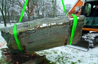 Runene på undersiden oppdages. Harald Martin Schie løfter den ca 2 tonn tunge steinen i båndgneiss Foto KHM