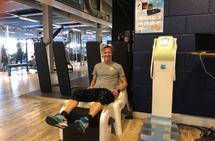 Gründer Jan Gisle Berger sitter på en stol med beina over sitt selvutviklede massasjeapparat, Z-rolleren