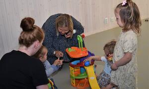Interiørarkitekt Siri Lise Sunde fortel om fargevalet i barnehagen til statsråd Guri Melby og dei andre gjestene under omvisinga i barnehagen. (Foto: Mariann Skau)