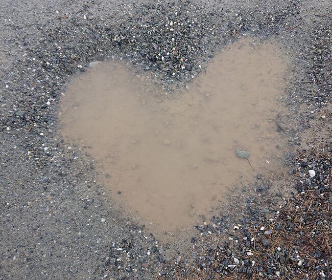 Sølepytt formet som hjerte på grusvei.