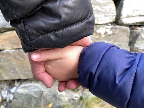 Vaksen og barn som held kvarandre i hendene