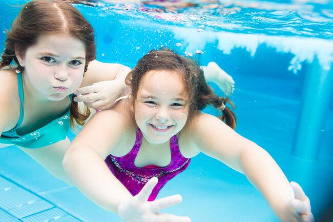 Two female friends swimming underwater