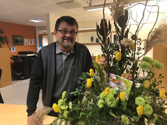 Trygve Karlsen sammen med blomsteroppsatsen som pynter opp i servicekontoret på Orkland rådhus.