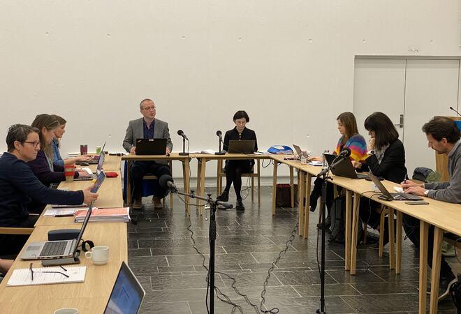 Personar rundt møtebord med koronaavstand.