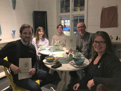 Fem personar rundt eit bord på Kafe Krydder.