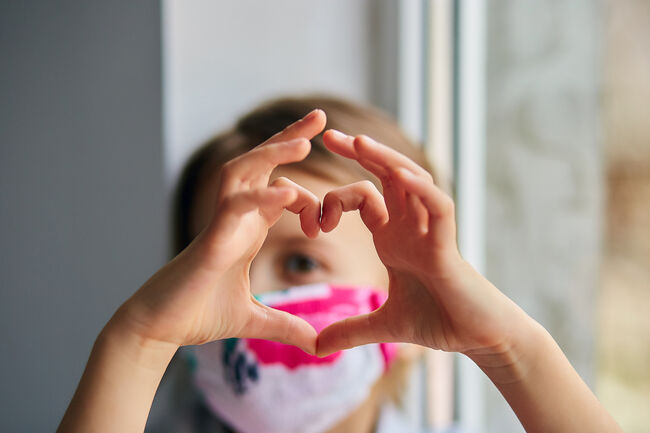 Bilde av jente med munnbind som lager hjerteform med hendene.