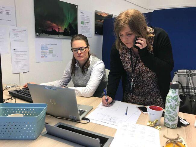Bilde av ansatte som betjener koronatelefonen.