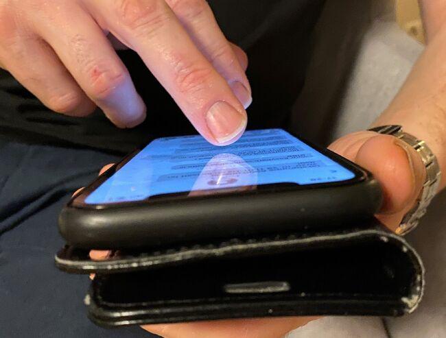 Person som ser på melding på mobilen