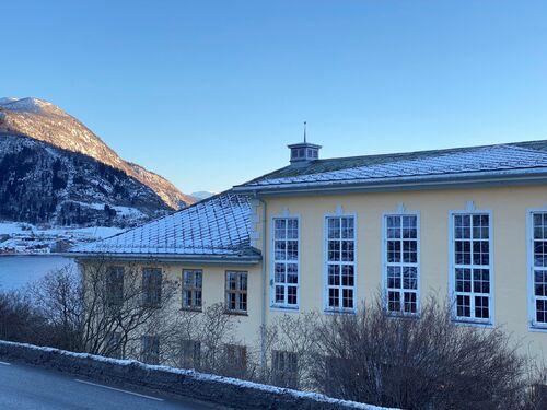 Tinghuset på Leikanger sett mot Hermansverk med sol på snødekte toppar.