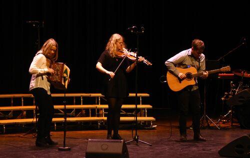 Tre musikkelevar strå på scena og spelar