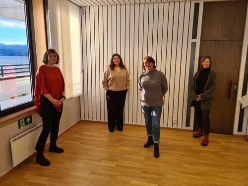 Fire personar oppstilte på eit kontor.